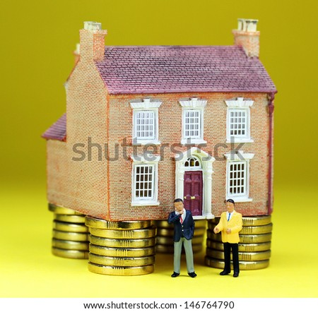 A real estate agent and a prospective buyer in front of a house on gold coin stilts, with the prospective buyer about to walk away, suggesting you can't win them all! - stock photo