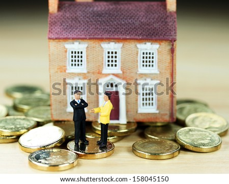 A real estate agent and a prospective buyer in front of a house resting on gold coins, with the prospective buyer not impressed with very negative body language, suggesting you can't win them all! - stock photo