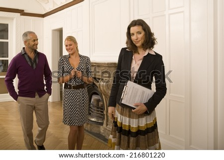 A real estate agent holding documents with a couple walking behind her