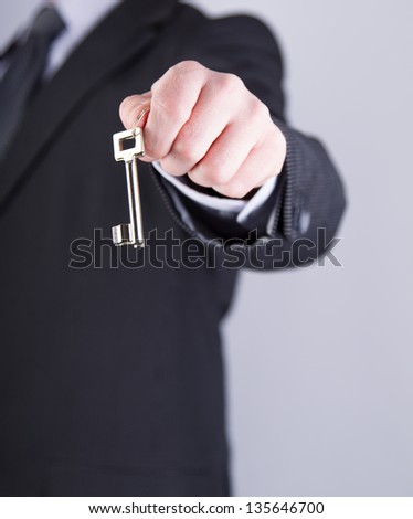 A real estate agent holds out a key of a new home to a lucky buyer - stock photo