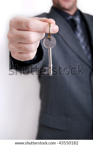 A real estate agent holds out the front door key of a new home to a lucky buyer. - stock photo