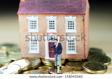 A real estate agent in front of a house  resting on gold coins, with a real thinkers pose, suggesting you have to find the buyers green button! - stock photo