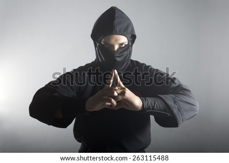 A real ninja shot on a smoke filled room and strobe light to achieve a dramatic effect. - stock photo
