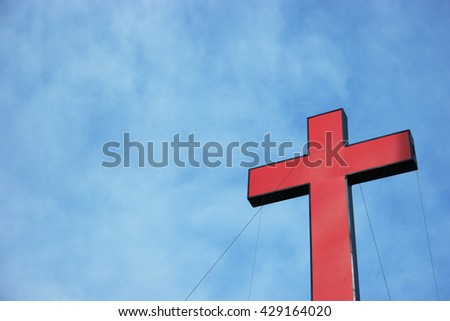 a real red cross or religion symbol cross shaped over a blue sky with clouds background as symbolic to God, Christ, Christianity, religious, faith, holy, spiritual, Jesus, belief or resurection - stock photo