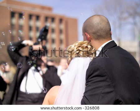 A real wedding couple and photographer. Bubbles filled the air. (Real wedding, 14MP camera) - stock photo