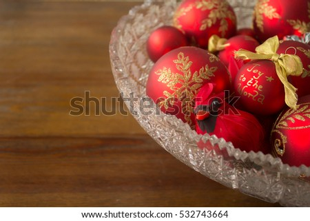 "A realistic cardinal decoration and decorative Christmas balls in a crystal bowl, featuring the words ""Joy to the world."" Photographed from the side. Includes copy space."