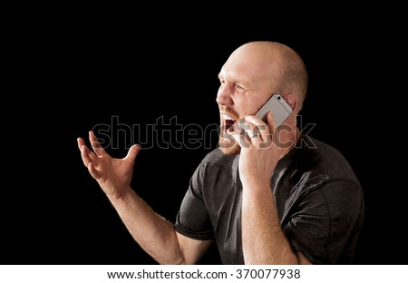 A really angry man talking on the phone - stock photo