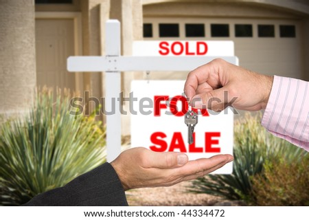 A Realtor hands over the keys to a new home buyer after the sale is final. - stock photo