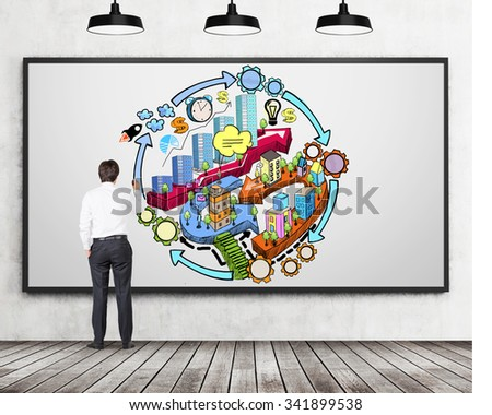 A rear view of businessman who is drawing a colourful business development flowchart on the concrete wall. There are three ceiling lights and wooden floor in the room. - stock photo
