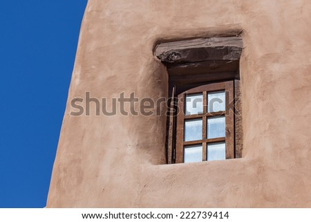 A recessed window in a traditional southwestern building with support beams and curved adobe wall. - stock photo