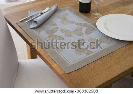A rectangular placemat with embroidered butterflies as design spread out on wooden table with napkin and utensils atop alongside empty dinner plate, wine glass, and a bottle of wine. - stock photo