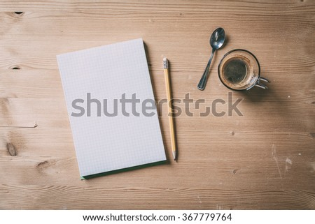 A recycled paper notebook checked with a black pencil with the eraser at the top and a cup of coffee with spoon, are arranged on a wooden table. View from the top - stock photo