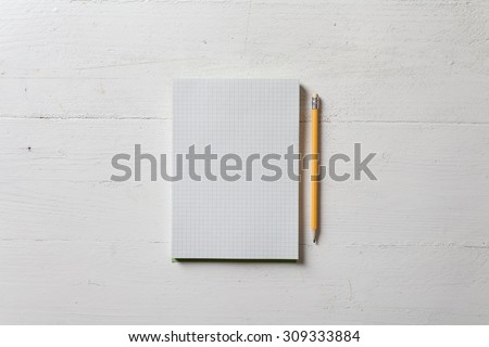 A recycled paper notebook checked with a black pencil with the eraser at the top, are arranged on a wooden table painted white. View from the top - stock photo
