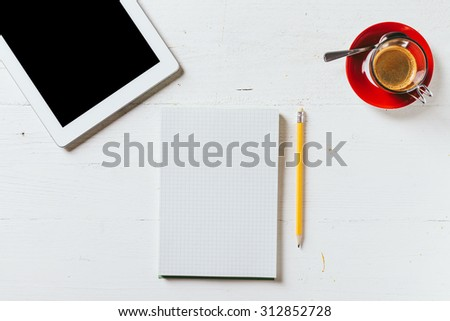 A recycled paper notebook squared, a black pencil with the eraser at the top and a cup of coffee with red saucer and spoon and a tablet, are arranged on a wooden table painted white. View from the top - stock photo
