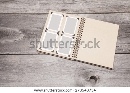 A recycled paper scrapbook with four vintage photos on one page sits on a rustic wooden background. The photos are simple solid colors and can easily be replaced with your content. - stock photo