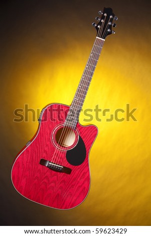 A red acoustic guitar isolated against a spotlight yellow background in the vertical format.