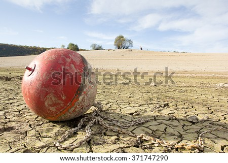 a red anchor buoy on a dry lake - stock photo