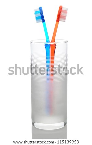 A red and blue toothbrush standing in a frosted water glass. Vertical format on a white background with reflection.