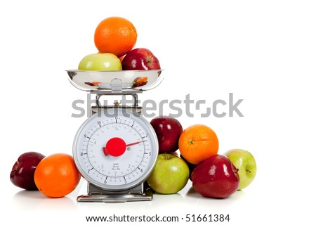 A red and green apple and orange on a scale with a white background