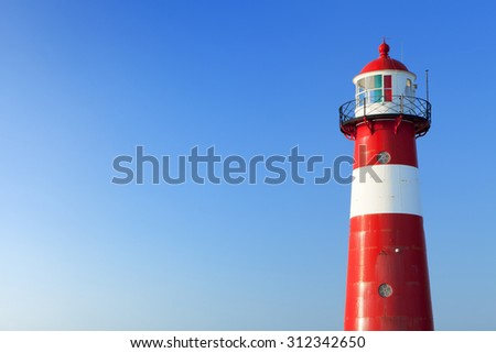 A red and white lighthouse at sea under a clear blue sky. Photographed near Westkapelle in Zeeland, The Netherlands. - stock photo
