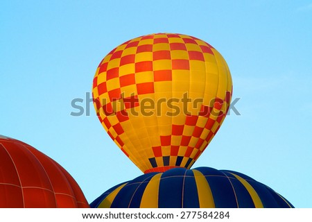 A red and yellow checkerboard colored hot air balloon is rising into the sky above a blue and yellow striped one. - stock photo