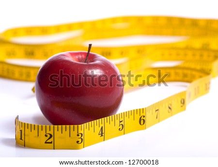 A red apple and a yellow tape meausure on a white background.  Dieting or healthy eating concept.