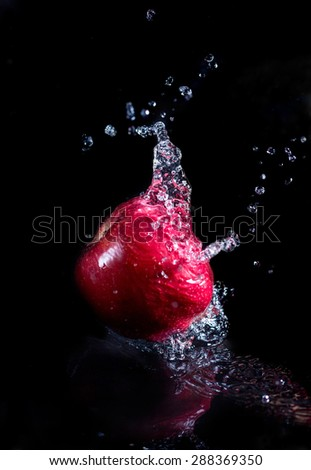 a red apple in juice/ water stream - stock photo