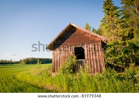 A red barn on a field next to the woods - stock photo