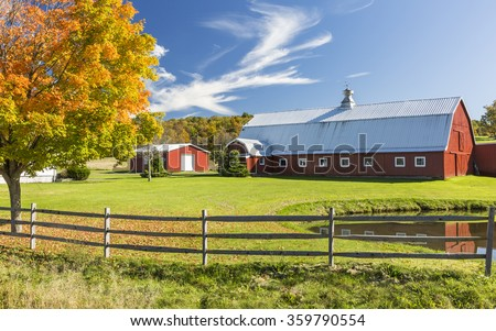 A red barn reflected in a pond with a colorful Autumn tree in the Catskills Mountains on New York