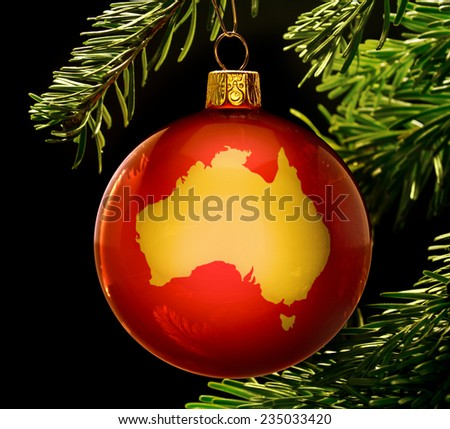 A red bauble with the golden shape of  Australia hanging on a christmas tree isolated on black.(series) - stock photo