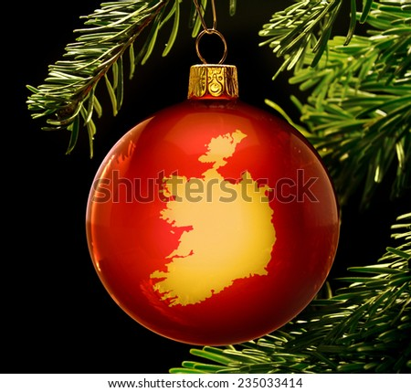 A red bauble with the golden shape of  Ireland hanging on a christmas tree isolated on black.(series) - stock photo