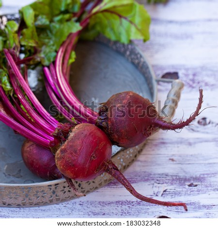 A red beetroots with some green leafs on a solid light wooden table - stock photo