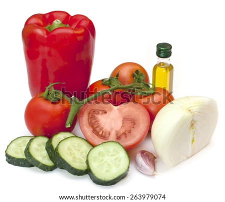 A red bell pepper, tomatoes, chopped cucumber, half an onion, a garlic clove and a small bottle of olive oil on white background (traditional Spanish gazpacho soup ingredients) - stock photo
