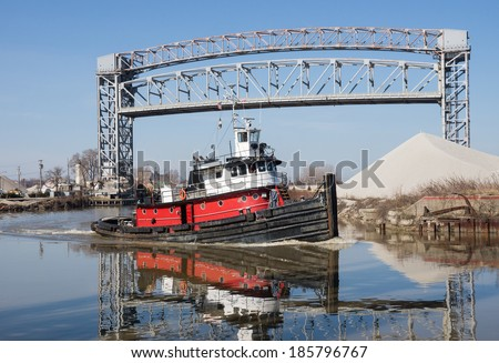 A red, black, and white tugboat makes it's way past a raised drawbridge and a mound of aggregate material as it heads for the open waters of Lake Erie from the Cuyahoga River in Cleveland, Ohio
