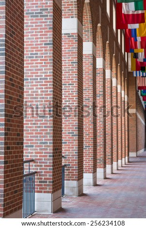 A red brick building entrance or hallway with international flags - stock photo