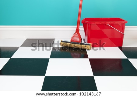 A red bucket and mop on a white and black checkered floor against a turquoise blue wall.