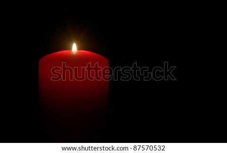A red candle over a black background - stock photo