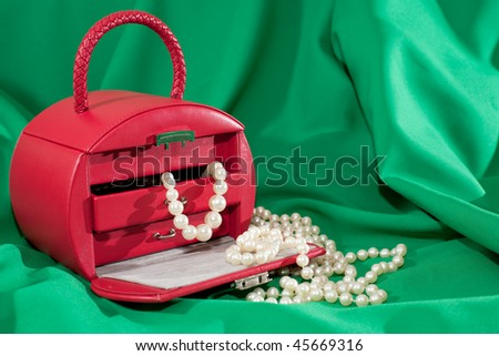 A red case with jewels is on the green background - stock photo