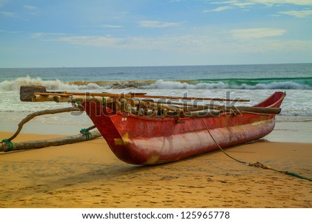 A red catamaran at the red-golden beach of Hikkaduwa on the beautiful tropical island Sri Lanka. In the background the Indian Ocean with shining turquoise and blue colors. - stock photo