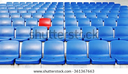 A red chair amidst rows of blue plastic spectator seats.