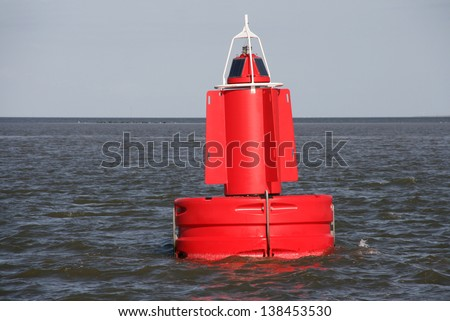 A red channel marker buoy in the water. - stock photo
