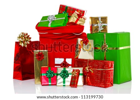 A red Christmas sack full of and surrounded by gift wrapped presents, isolated on a white background. - stock photo