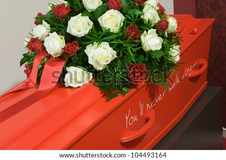 A red coffin in a morgue with a flower arrangement - stock photo
