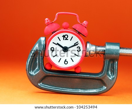 A red colored  alarm clock placed in a Grey clamp against a pastel orange background, asking the question do you manage your time effectively. - stock photo