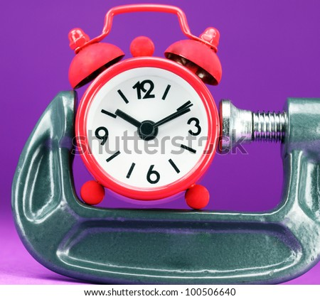 A red colored  alarm clock placed in a Grey clamp against a pastel purple background, asking the question do you manage your time effectively. - stock photo