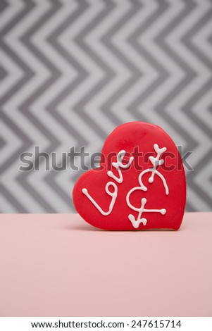 A red Cookie printed with 'Love' on a grey chevron background with pink foreground - stock photo