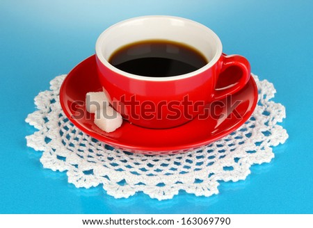 A red cup of strong coffee on blue background - stock photo