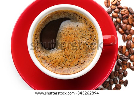 A red cup of tasty drink and scattered coffee grains, close-up, top view - stock photo