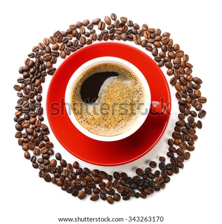 A red cup of tasty drink and scattered coffee grains in the shape of circle, isolated on white, top view - stock photo