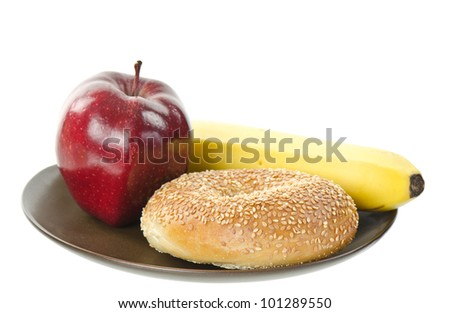 A Red Delicious apple, a sesame seed bagel and a banana on a brown earthenware plate, - stock photo
